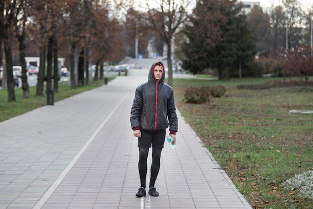 Uomo di vista frontale che cammina e che tiene una bottiglia di acqua Foto Gratuite