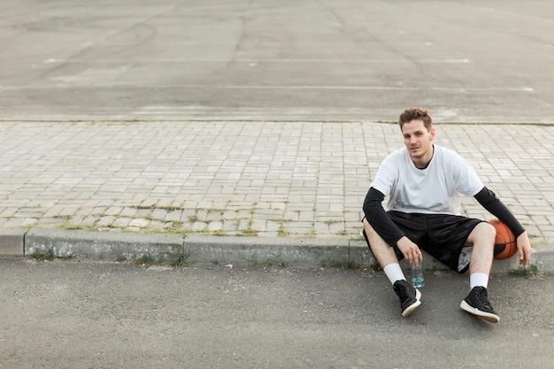 Uomo di vista frontale che si siede con una pallacanestro Foto Gratuite