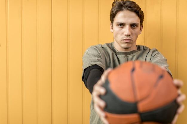 Uomo di vista frontale che tiene una pallacanestro Foto Gratuite