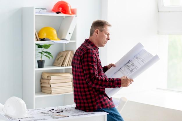 Uomo di vista laterale che controlla progetto architettonico Foto Gratuite