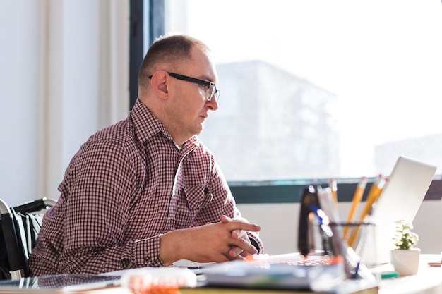 Uomo disabile adulto che lavora all'ufficio Foto Gratuite