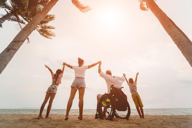 Uomo disabile in sedia a rotelle con la sua famiglia sulla spiaggia. sagome al tramonto Foto Premium
