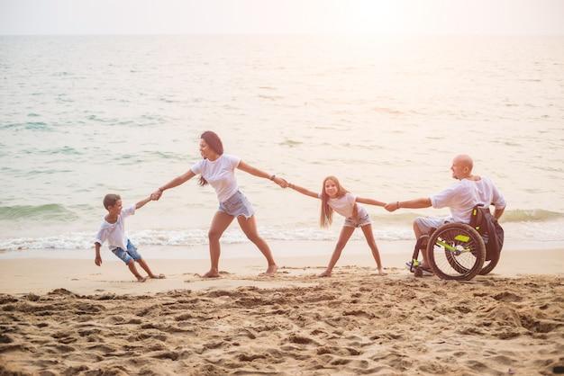 Uomo disabile in sedia a rotelle con la sua famiglia sulla spiaggia. Foto Premium