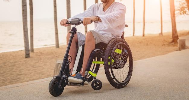 Uomo disabile in sedia a rotelle con scooter elettrico sulla spiaggia Foto Premium
