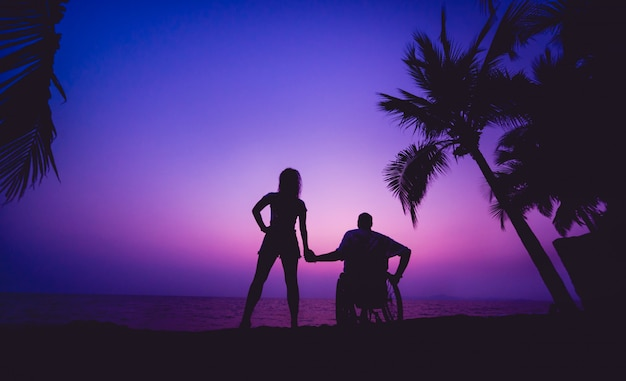 Uomo disabile in sedia a rotelle con sua moglie sulla spiaggia. sagome al tramonto Foto Premium