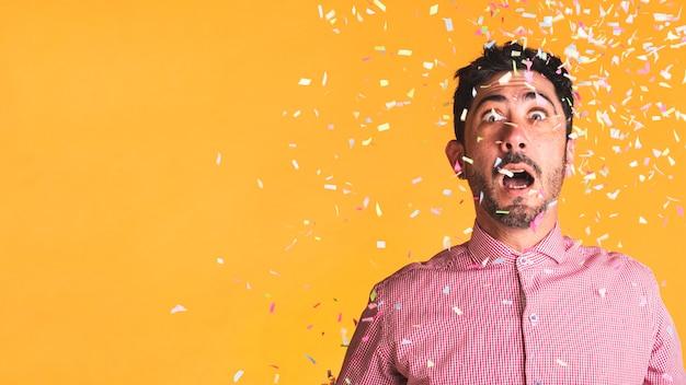 Uomo e coriandoli su sfondo arancione con spazio di copia Foto Gratuite