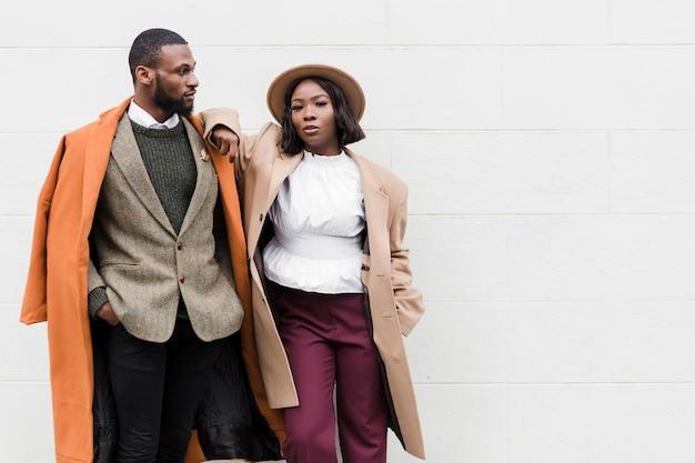 Uomo e donna alla moda che posano con lo spazio della copia Foto Gratuite