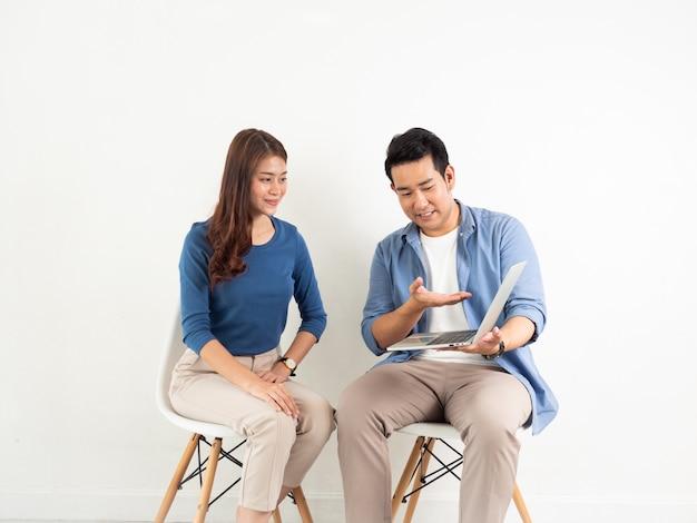 Uomo e donna asiatici che parlano con il computer portatile per l'affare su fondo bianco Foto Premium