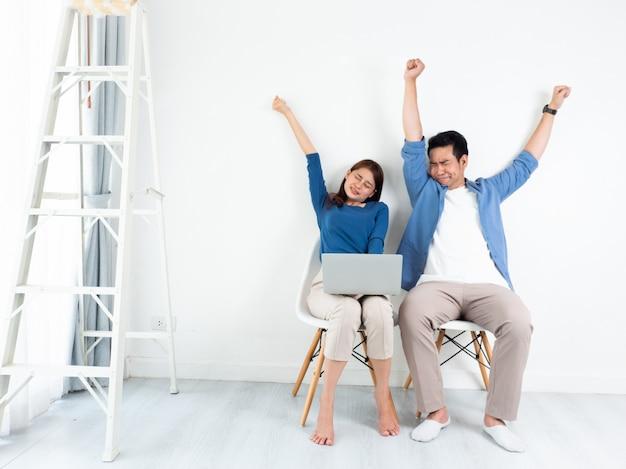 Uomo e donna asiatici che parlano noioso e sonnolento con il computer portatile per l'affare su fondo bianco Foto Premium