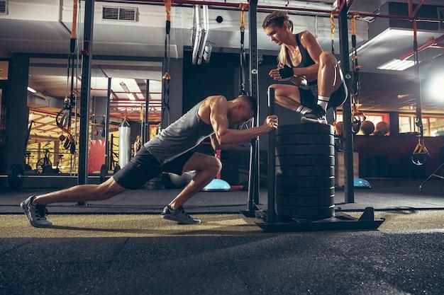 Uomo e donna atletici con manubri che si allenano e che si esercitano in palestra. Foto Gratuite