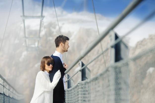 Uomo e donna che attraversano insieme il ponte Foto Gratuite