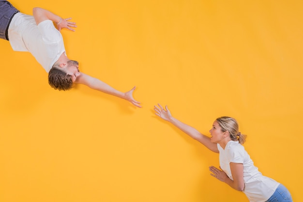 Uomo e donna che cercano di raggiungere l'altro Foto Gratuite