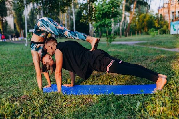 Uomo e donna che fanno insieme yoga nel parco all'aperto. uomo che bacia una donna Foto Premium