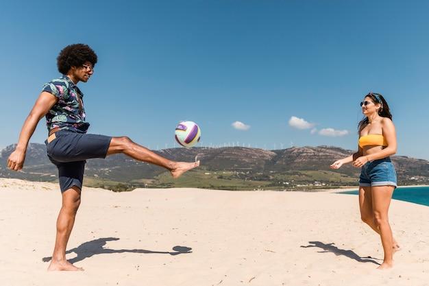 Uomo e donna che giocano a calcio sulla spiaggia di sabbia Foto Gratuite
