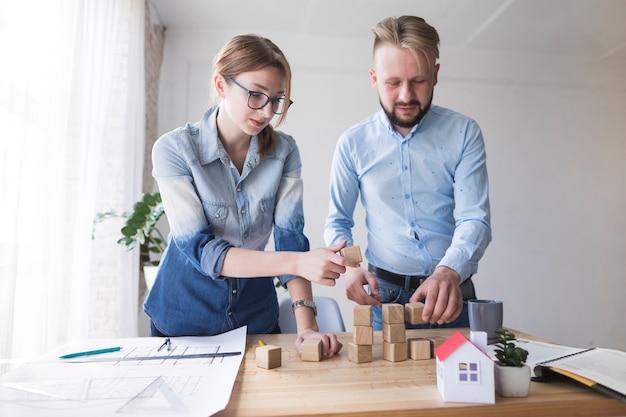 Uomo e donna che impilano blocco di legno sullo scrittorio funzionante all'ufficio Foto Gratuite