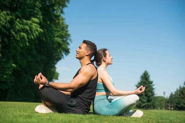 Uomo e donna che praticano yoga all'aperto Foto Gratuite