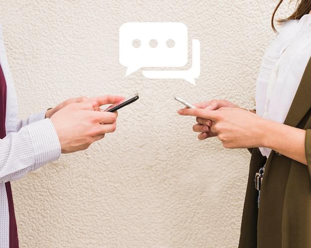 Uomo e donna che scambiano messaggi sul cellulare Foto Gratuite