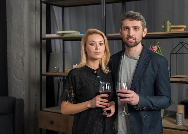 Uomo e donna con bicchieri di vino in camera Foto Gratuite