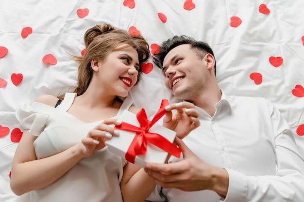 Uomo e donna con regalo a letto con coriandoli a forma di cuore Foto Premium