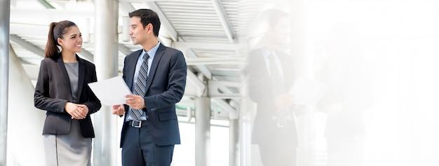 Uomo e donna di affari che discutono di lavoro in movimento Foto Premium