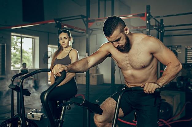 Uomo e donna durante gli esercizi in palestra. Foto Gratuite
