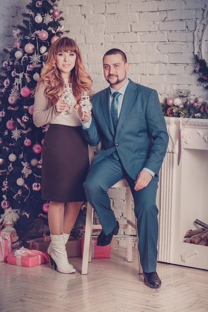 Uomo e donna in camera con albero di natale e camino Foto Premium
