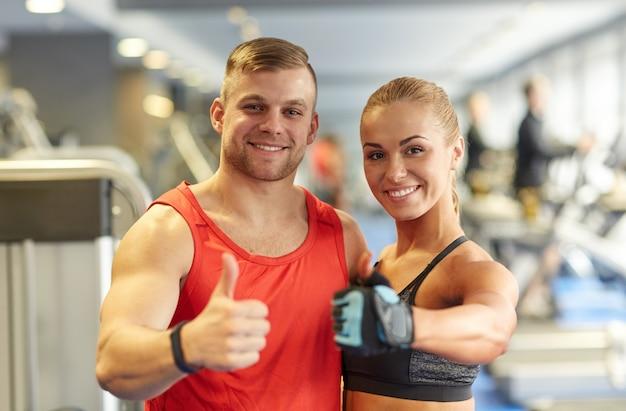 Uomo e donna sorridenti che mostrano i pollici su nella palestra Foto Premium