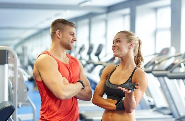 Uomo e donna sorridenti che parlano in palestra Foto Premium