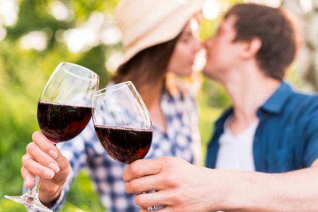 Uomo e donna tintinnio di bicchieri con vino Foto Gratuite