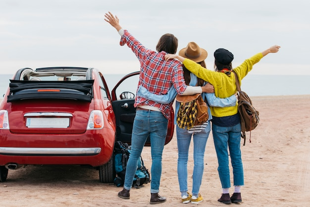 Uomo e donne che si abbracciano vicino auto sulla costa del mare Foto Gratuite