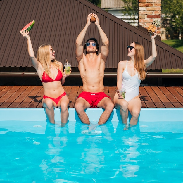 Uomo e donne in posa in costume da bagno Foto Gratuite