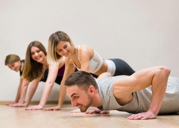 Uomo e gruppo di donne che si allenano insieme Foto Gratuite