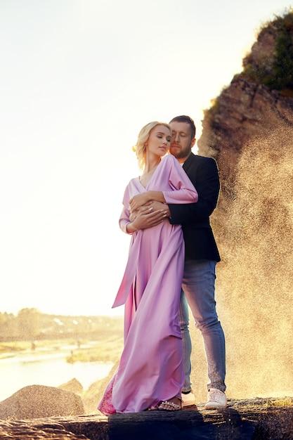 Uomo e una donna che abbraccia in estate al tramonto Foto Premium