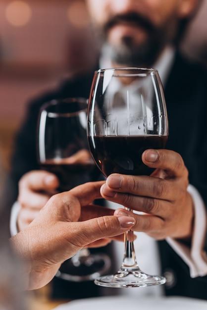 Uomo e una donna che tiene insieme un bicchiere di vino rosso in primo piano. Foto Premium