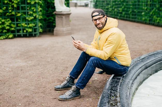 Uomo eccitato con la barba e il viso affascinante che indossa abiti alla moda che riposa all'aperto Foto Premium