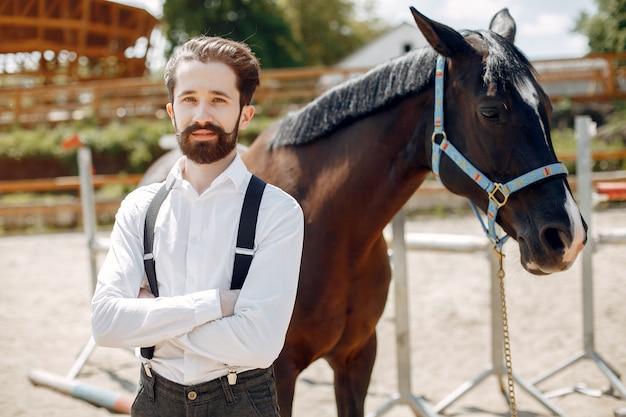 Uomo elegante che sta accanto al cavallo in un ranch Foto Gratuite
