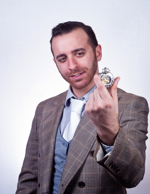 Uomo elegante guardando il suo vecchio orologio da tasca Foto Premium