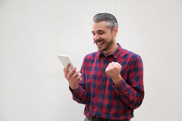 Uomo emozionante che per mezzo della compressa digitale Foto Gratuite