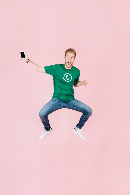 Uomo emozionante con lo smartphone che salta sul contesto rosa Foto Gratuite