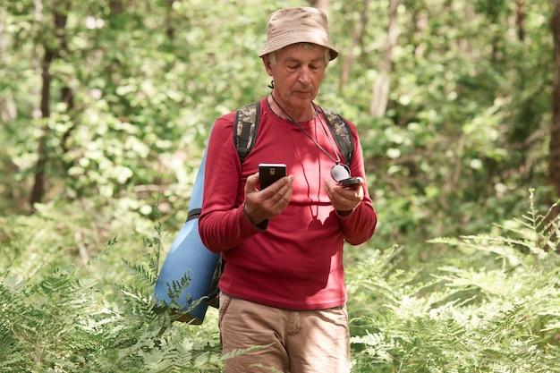 Uomo entusiasta serio che vaga nella foresta, con bussola e smartphone in mano, scegliendo il suo itinerario di viaggio Foto Premium