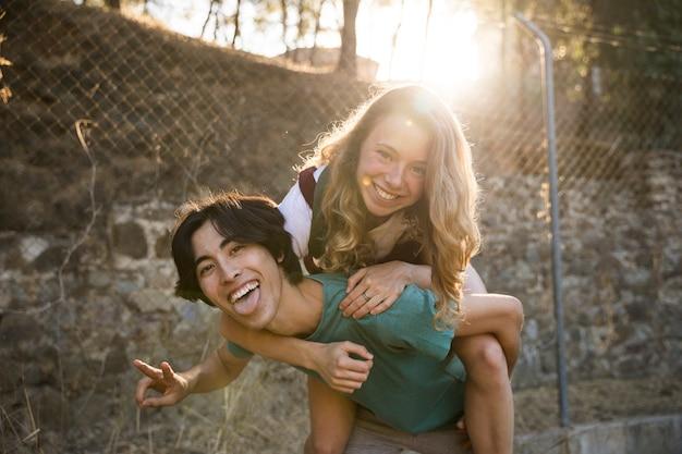 Uomo etnico con la ragazza sulla parte posteriore che ride della macchina fotografica Foto Gratuite