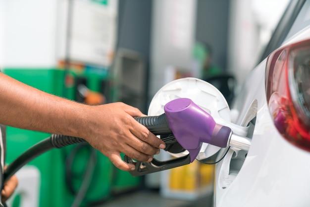Uomo fare rifornimento di auto nella stazione di benzina per il viaggio Foto Premium