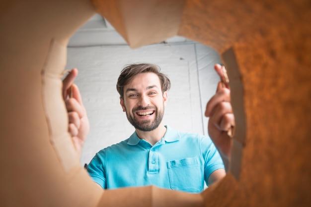 Uomo felice che osserva all'interno del sacco di carta Foto Gratuite