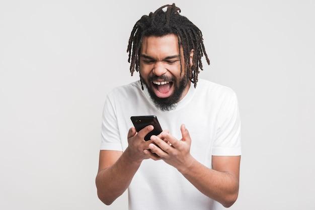 Uomo felice che osserva sullo smartphone Foto Gratuite