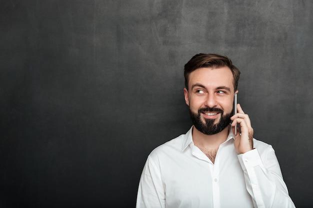 Uomo felice che parla sul telefono cellulare che ha conversazione piacevole che guarda da parte sopra lo spazio della copia della grafite Foto Gratuite