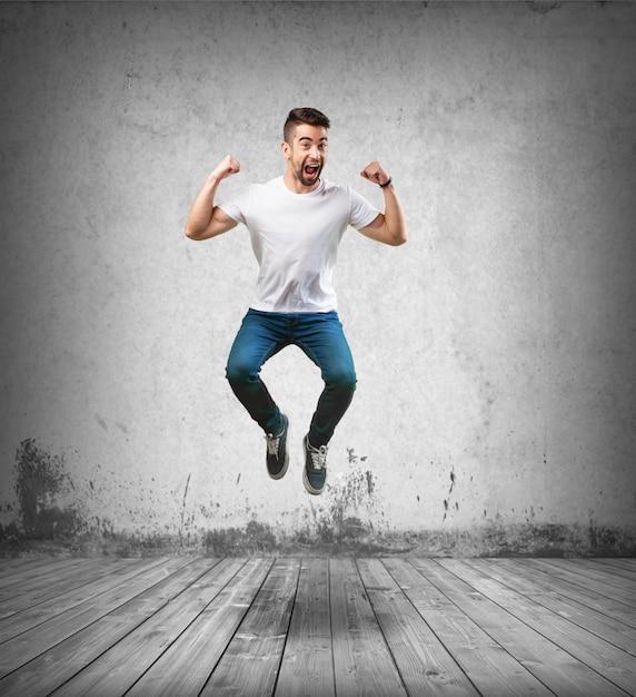 Uomo felice che salta sul pavimento di legno Foto Gratuite