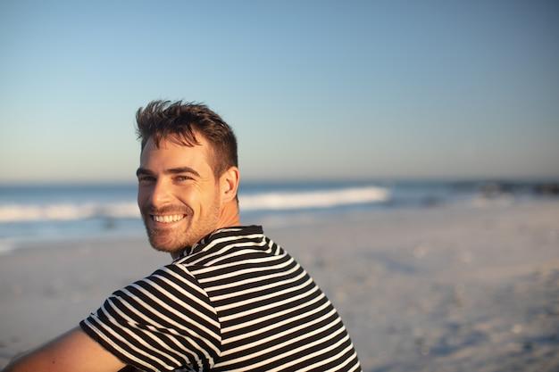 Uomo felice che si distende sulla spiaggia Foto Gratuite