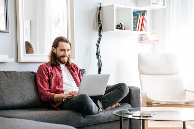 Uomo felice che si siede sul sofà e che per mezzo del computer portatile a casa Foto Gratuite