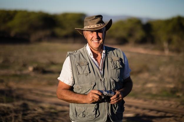 Uomo felice che sta con la macchina fotografica durante la vacanza di safari Foto Gratuite