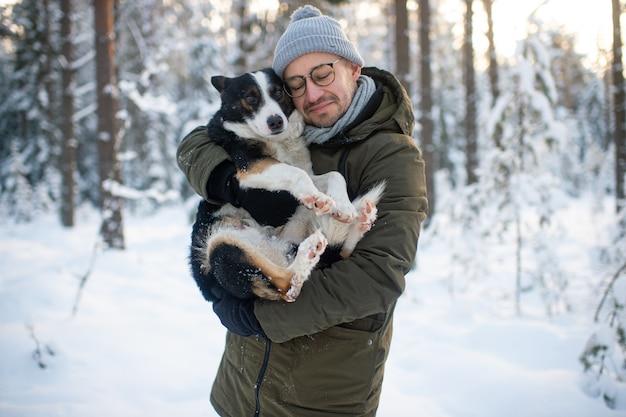 Uomo felice che tiene cane adorabile in sue mani in foresta nevosa. ragazzo sorridente che abbraccia cucciolo adorabile in legno di inverno. Foto Premium